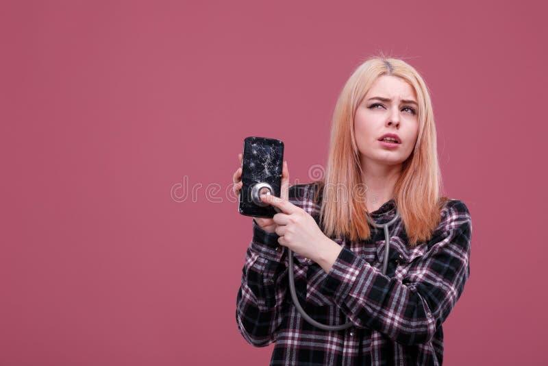 Uma moça aplica um estetoscópio a um telefone quebrado e com um olhar pensativo olha acima Fundo cor-de-rosa fotos de stock royalty free