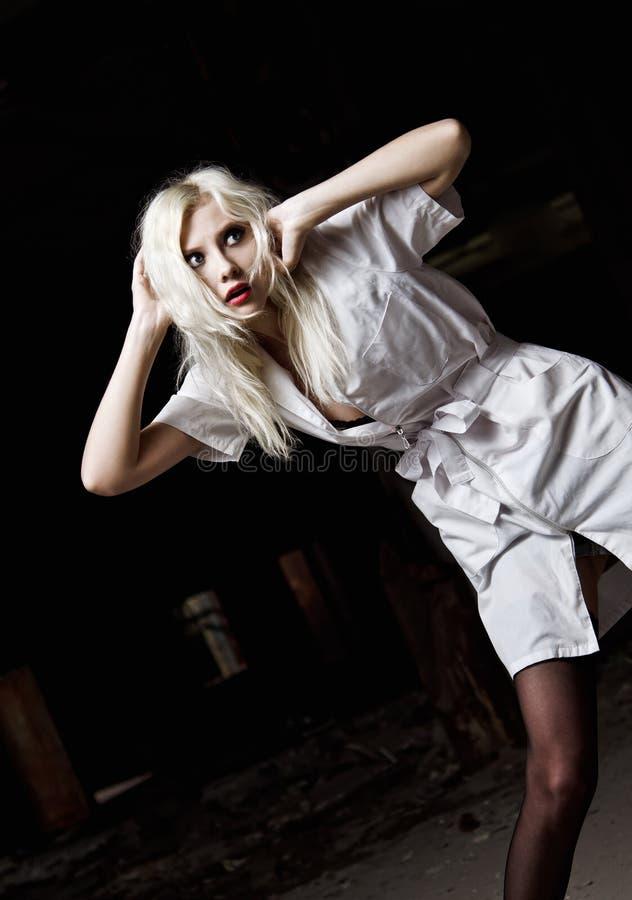 Uma moça assustado bonita na imagem da enfermeira entre a obscuridade imagens de stock