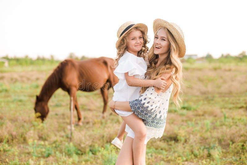 Uma moça bonita, com cabelo encaracolado leve em um chapéu de palha com uma irmã mais nova que abraça e que ri perto dos cavalos imagem de stock royalty free