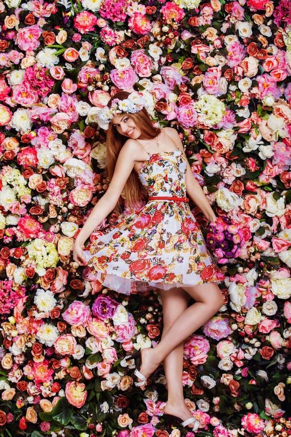 Uma moça bonita com ramalhete das flores perto de uma parede floral imagem de stock royalty free