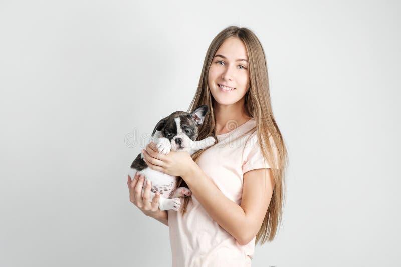 Uma moça bonita está guardando um cachorrinho de um buldogue francês imagens de stock royalty free