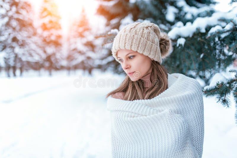 Uma moça bonita está no inverno na manta branca acima envolvida floresta Chapéu morno, árvores verdes na neve no fundo fotografia de stock