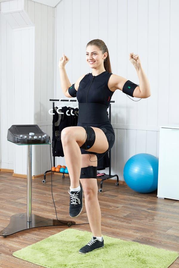 Uma moça bonita executa um exercício em um músculo bonde imagem de stock