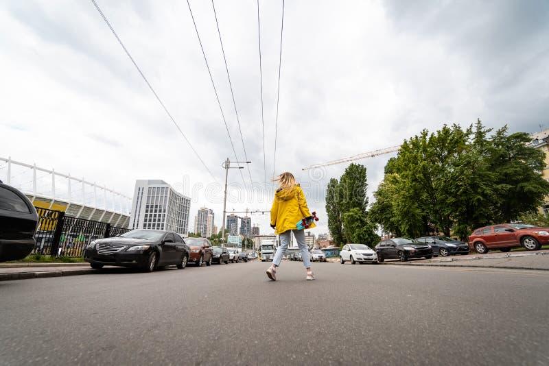 Uma moça bonita guarda um skate e cruza a estrada fotografia de stock