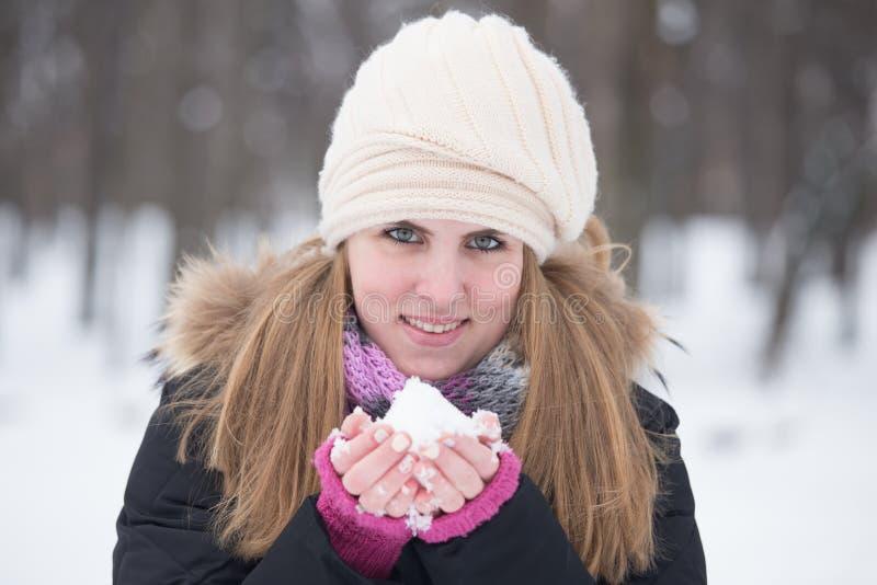 Uma moça bonita que guarda a neve à disposição e para olhar a câmera fotos de stock