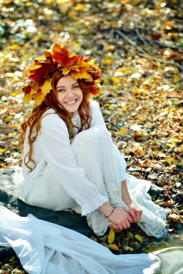 Uma moça bonita vestiu-se no branco, vestindo uma grinalda das folhas do amarelo, sentando-se nas folhas da queda em um dia ensol imagens de stock royalty free