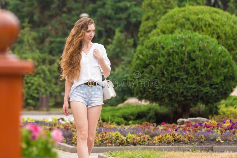 Uma moça com uma bolsa branca dos ladys está andando ao longo de uma aleia bonita imagem de stock royalty free