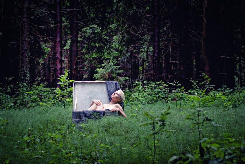 Uma moça com cabelo branco curto está sentando-se em uma grande mala de viagem no meio da floresta fotografia de stock