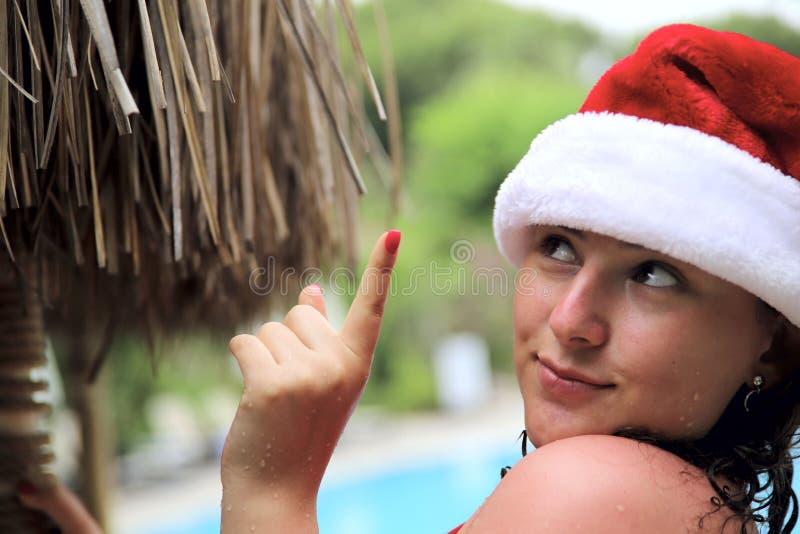 Uma moça com cabelo encaracolado em um maiô e em um chapéu vermelhos de Santa é de sorriso e apontando um dedo em algo foto de stock royalty free