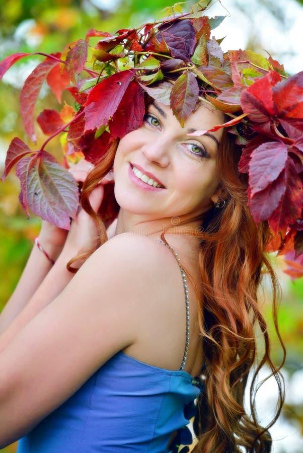 Uma moça com cabelo longo em uma grinalda da folha vermelha e verde que olha sobre o ombro, o levantamento e o sorriso imagens de stock royalty free