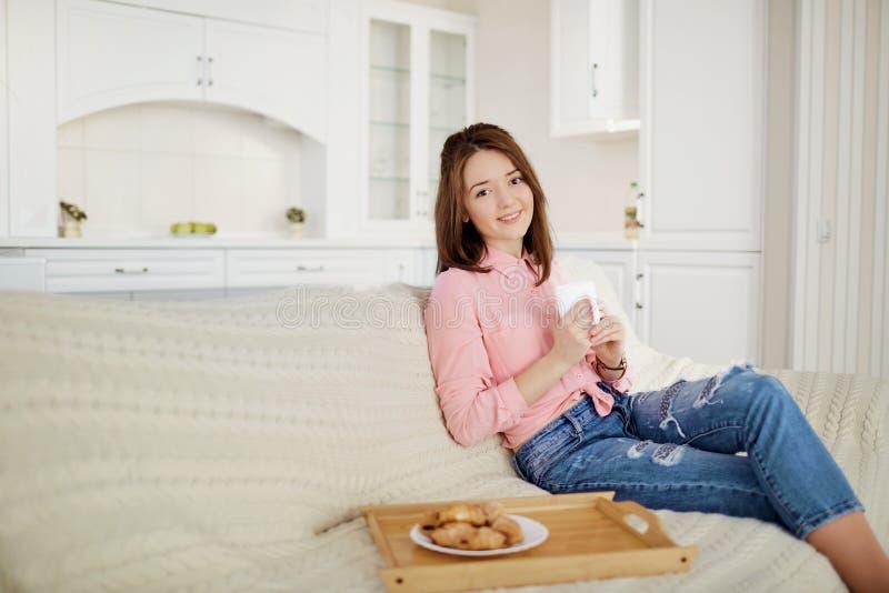 Uma moça com uma caneca de bebida quente senta-se na sala imagem de stock royalty free