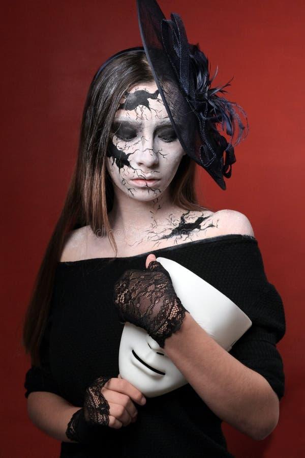 Uma moça com composição ao estilo de Dia das Bruxas está guardando uma máscara branca As quebras pretas são pintadas na cara e no foto de stock royalty free