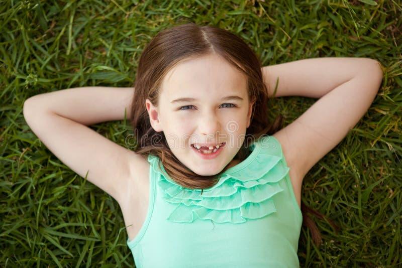Uma moça com um dente faltante está encontrando-se nela para trás na grama fotos de stock royalty free