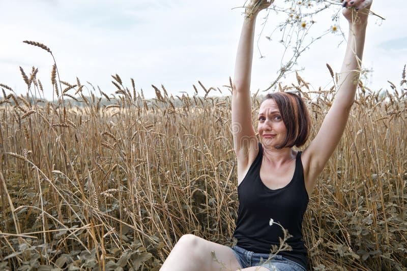 Uma moça com um ramalhete das flores que sentam-se perto de um campo de trigo Escolhe fora usin do amor das pétalas e querer sabe imagem de stock
