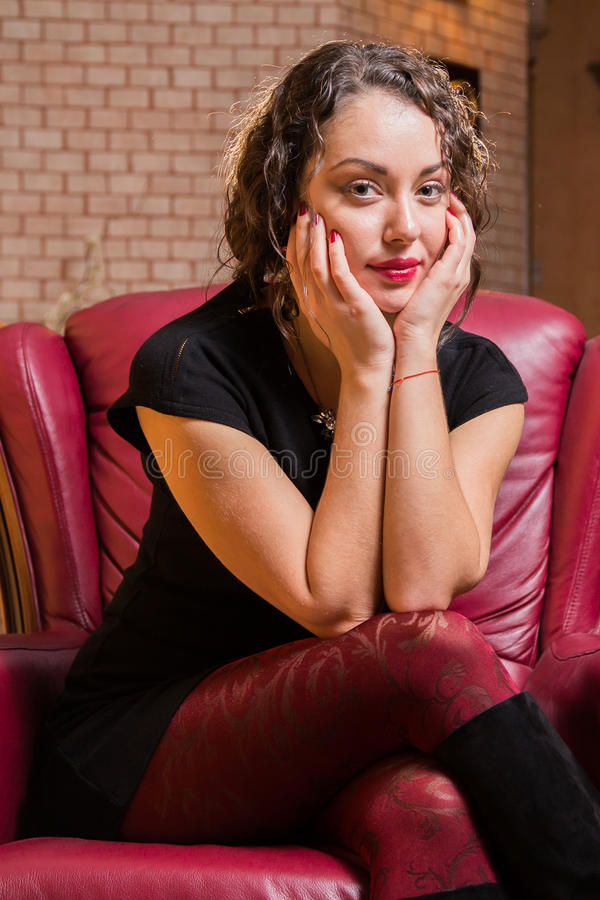 Uma moça com um vidro do vinho em um ajuste bonito fotos de stock royalty free
