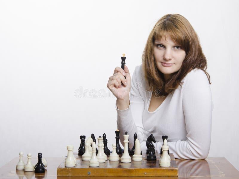 Uma moça com uma figura da rainha, na placa de xadrez fotos de stock