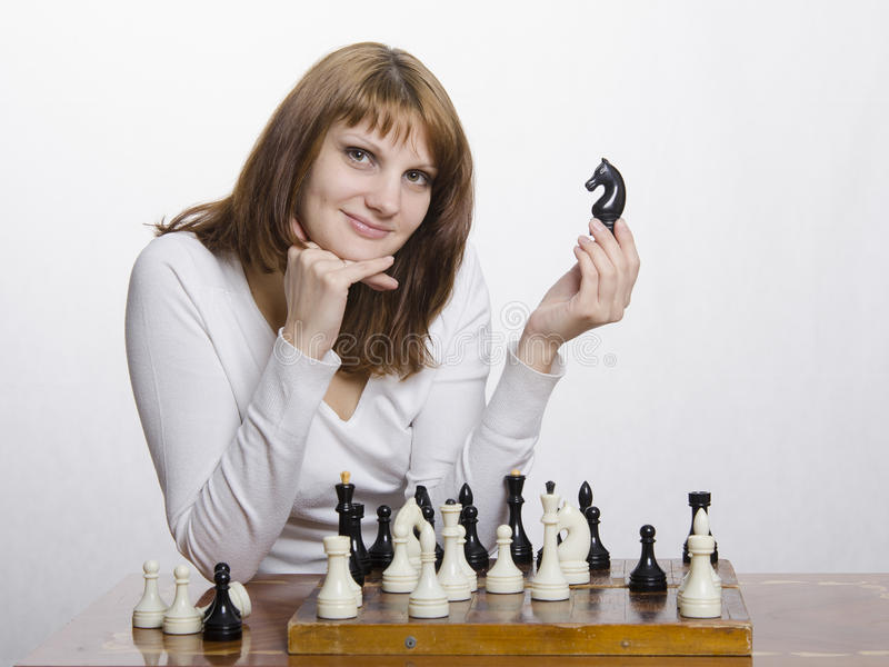 Uma moça com uma figura de um cavalo, na placa de xadrez fotos de stock