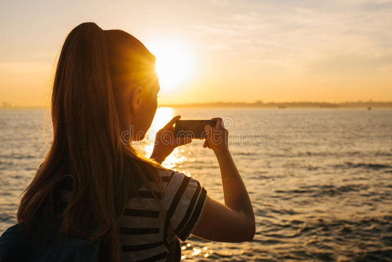 Uma moça com uma trouxa representa no telefone uma ideia bonita do mar e do por do sol Imagem para a memória descanso imagens de stock royalty free