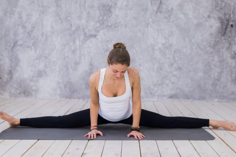 Uma moça desportivo que estica os pés, classe da ioga Mulher loura que senta-se na guita foto de stock