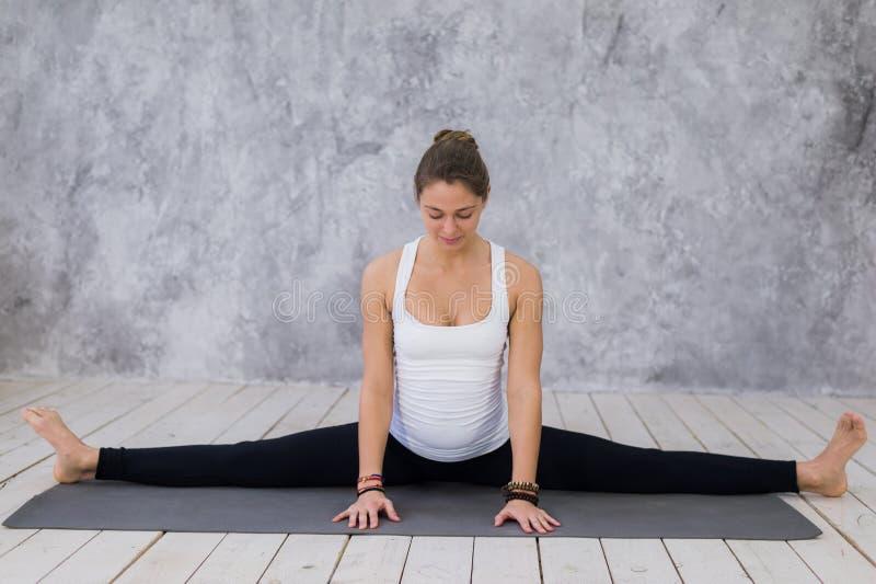 Uma moça desportivo que estica os pés, classe da ioga Mulher loura que senta-se na guita imagens de stock royalty free
