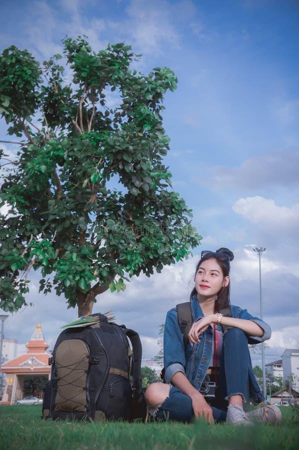 Uma moça do viajante que senta-se sob uma árvore relaxa o tempo e o looin imagem de stock royalty free