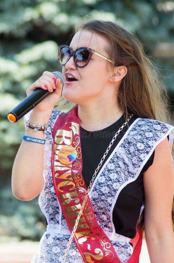 Uma moça em uma farda da escola festiva, executando em uma competição do karaoke em um parque da cidade foto de stock