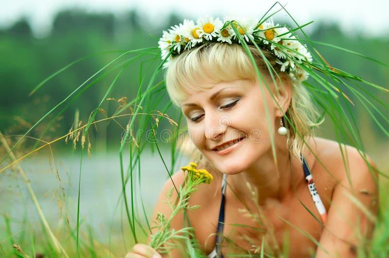Uma moça em uma grinalda das camomilas encontra-se em um prado verde Cara bonita sonhadora fotos de stock royalty free