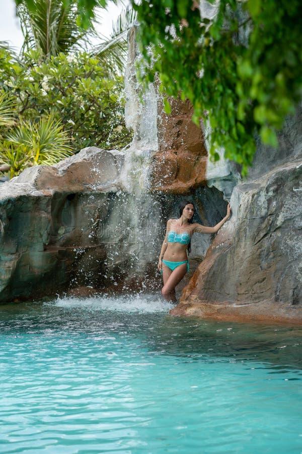 Uma moça em uma posição do maiô sob uma cachoeira artificial na associação no local fotos de stock royalty free