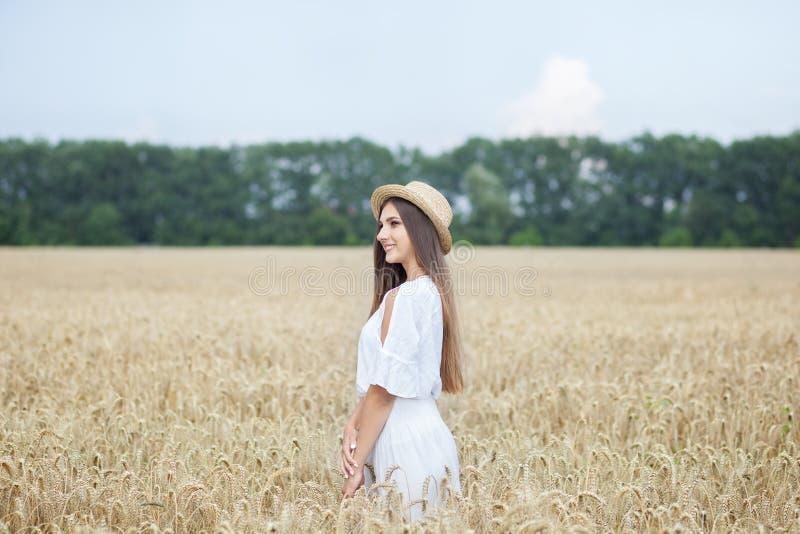 Uma moça em um chapéu é um barqueiro que aprecia a natureza de um campo de trigo Menina bonita nas corridas brancas do vestido no foto de stock royalty free