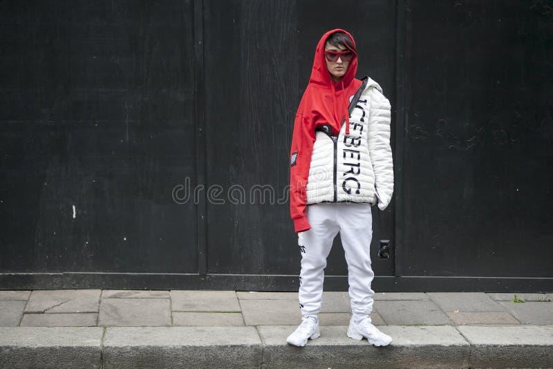 Uma moça em um hoodie vermelho, os vidros e um revestimento de esportes do branco firmam poses do iceberg na frente da parede pre imagem de stock