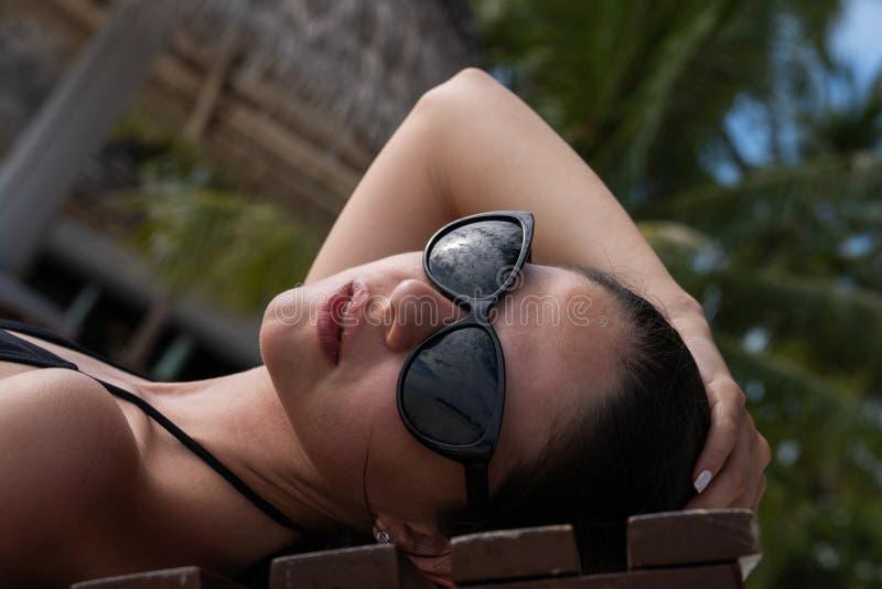 Uma moça em um maiô preto está encontrando-se em um vadio e em tomar sol fotografia de stock
