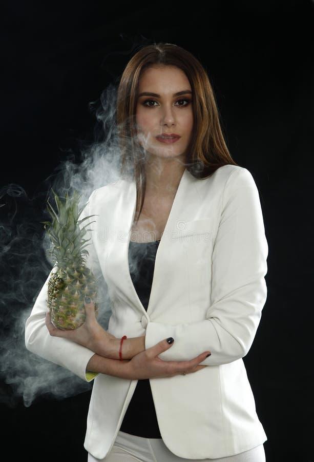 Uma moça em um revestimento branco guarda um abacaxi em seus mãos e sorrisos em um fundo preto, coberto com o vapor do fumo foto de stock royalty free
