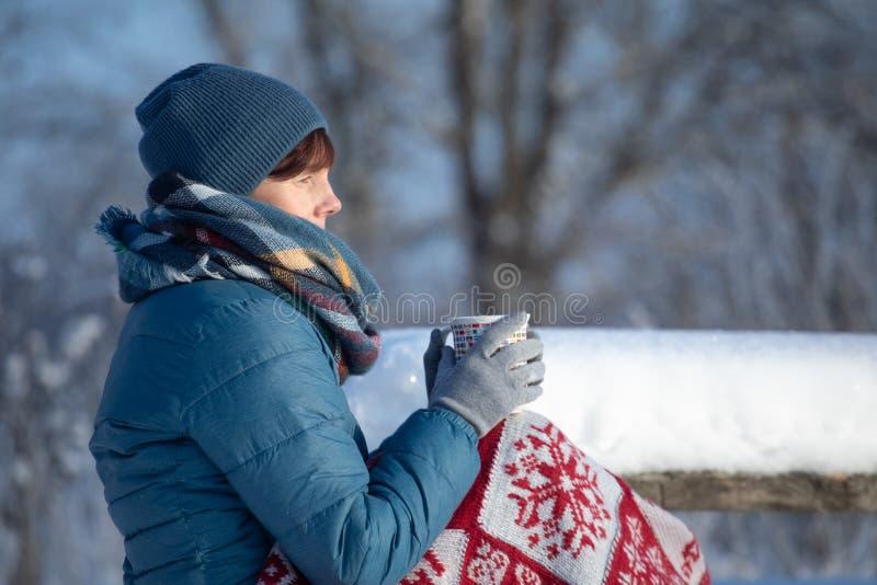 Uma moça em um vermelho em uma manta vermelha senta-se nos bancos de um rio com uma caneca de chá quente, de café, e de uma bebid fotos de stock