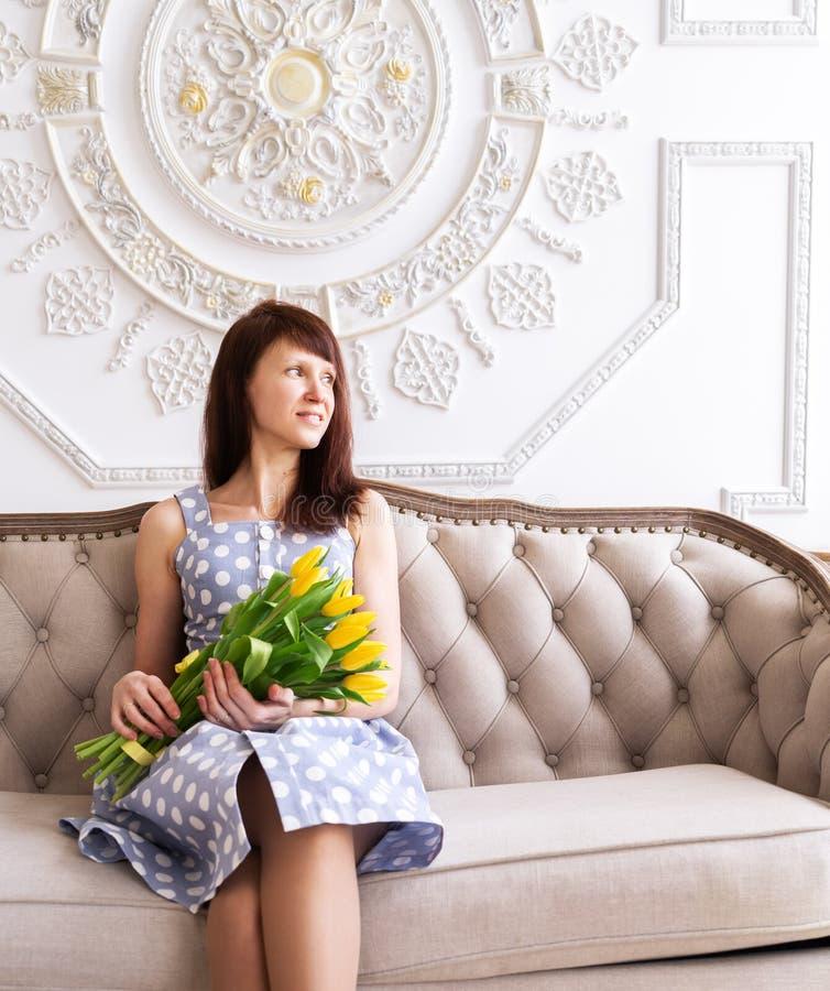 Uma moça em um vestido azul com um grande ramalhete de tulipas amarelas está sentando-se em um sofá do vintage contra o fundo imagens de stock royalty free