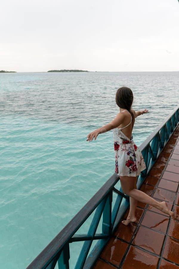 Uma moça em um vestido está estando em um restaurante do mar A ilha tem o tempo chuvoso foto de stock royalty free