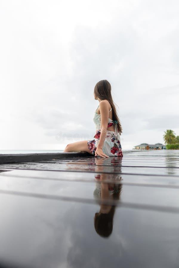 Uma moça em um vestido senta-se em uma ponte de madeira e em olhares no oceano A ilha é nebulosa imagem de stock royalty free