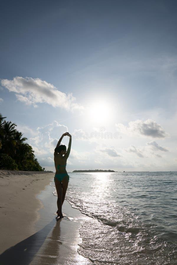 Uma moça está estando belamente em um maiô na borda da água e está tomando sol no sol foto de stock royalty free
