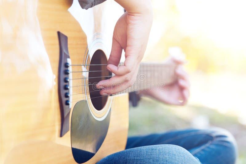 Uma moça está jogando a guitarra e canta uma música no campo de grama foto de stock