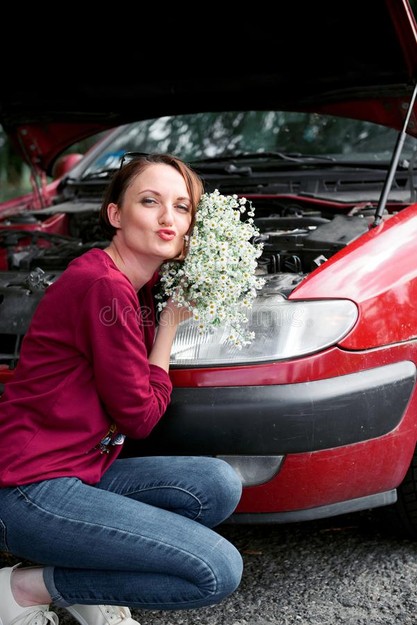 Uma moça está perto de um carro quebrado e dá-lhe flores fotos de stock