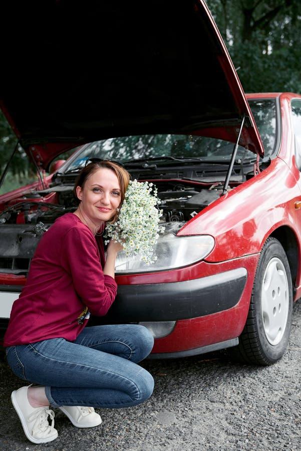 Uma moça está perto de um carro quebrado e dá-lhe flores imagem de stock