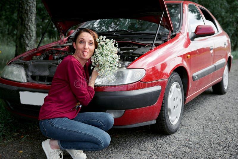Uma moça está perto de um carro quebrado e dá-lhe flores fotografia de stock royalty free