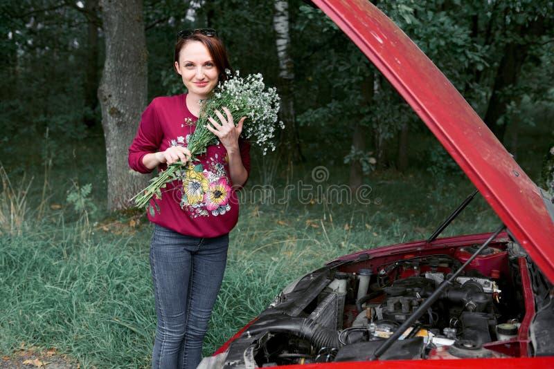 Uma moça está perto de um carro quebrado e dá-lhe flores imagens de stock