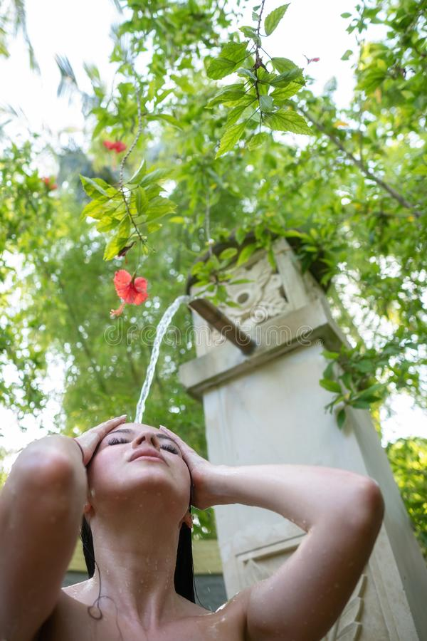 Uma moça está tomando um chuveiro fora fotografia de stock royalty free