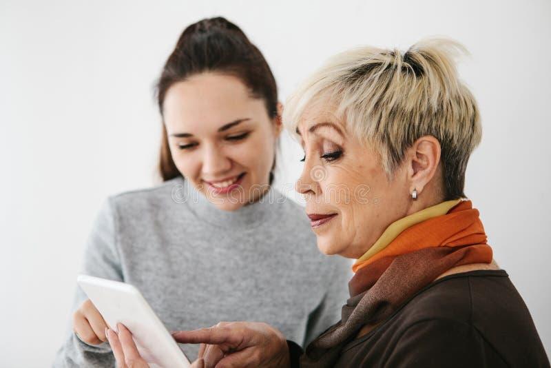 Uma moça explica a uma mulher idosa como usar uma tabuleta ou mostra alguma aplicação ou ensina-lhe como usar a foto de stock royalty free