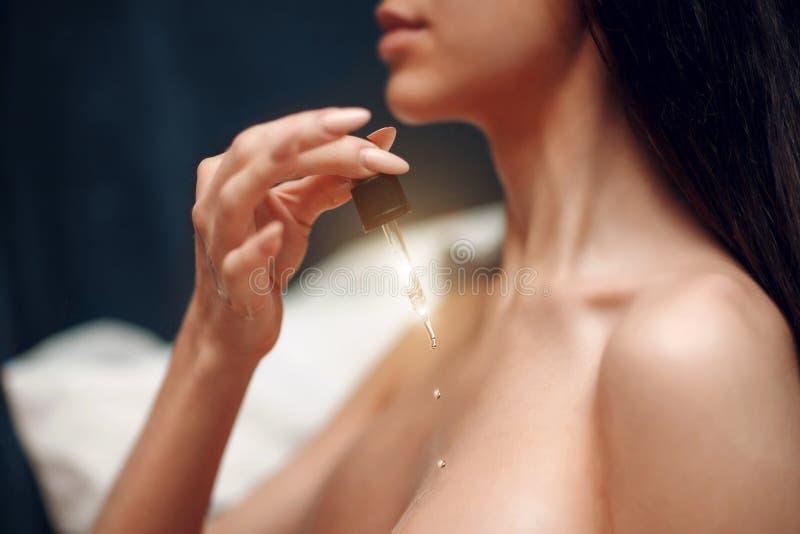 Uma moça guarda uma pipeta com óleo cosmético Conceito do cuidado de pele fotografia de stock