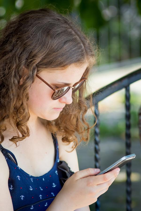 Uma moça guarda um telefone em suas mãos Uma comunicação usando um smartphone Entretenimento moderno no Internet_ imagens de stock royalty free