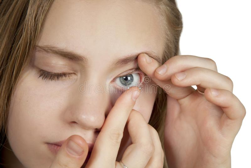 Uma moça introduz lentes de contato em seus olhos fotografia de stock royalty free