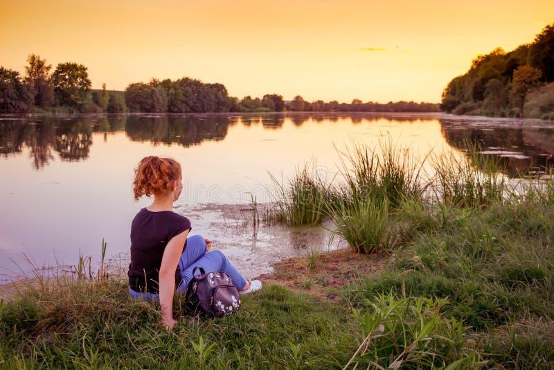 Uma moça no banco de rio admira a natureza durante o sunset_ imagens de stock royalty free