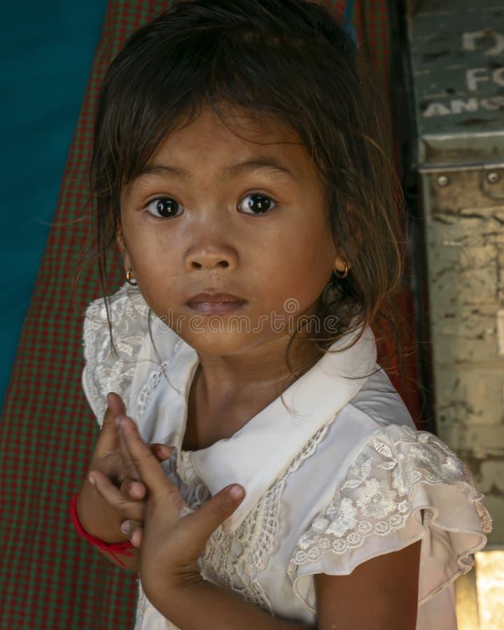 Uma moça olha na câmera enquanto acompanha sua mãe para adorar em Angkor Wat fotografia de stock royalty free