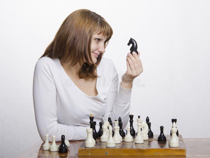 Uma moça olha o divertimento na estátua deste cavalo, sentando-se na placa de xadrez foto de stock